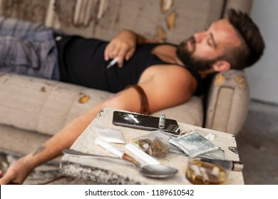 Passed out drug addict lying on the couch after shooting up with heroin; junkie overdosed with intravenous heroin injection. Focus on the smart phone