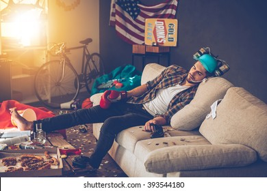 Passed out. Young handsome man in boxing glove and beer hat napping on sofa in messy room after party