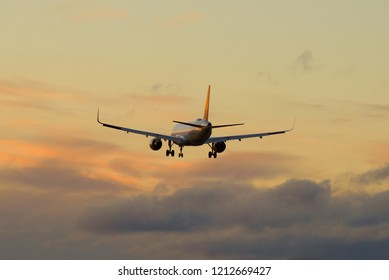 A passenger aircraft flies into the evening sky