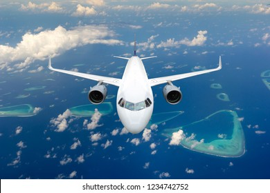 Passenger aircraft in flight. The plane flying high above the sea. Front view.