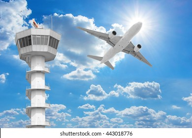 Passenger aircraft  flying above air traffic control tower against blue sky