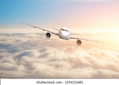 Passenger aircraft flying above the clouds horizon sky with bright sunset colors.