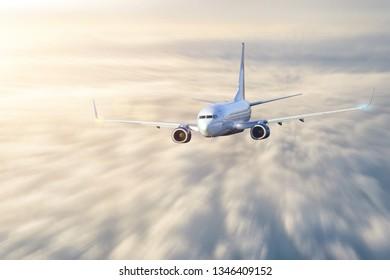 Passenger aircraft in motion blur flies cloudscape evening light before sunset