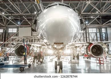 Passenger aircraft, nose close up. Maintenance of engine and fuselage repair in airport hangar.
