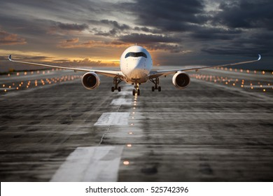Passenger aircraft on the airport runway. Plane takes off at the sunset time. Airplane front view.