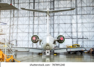 Passenger aircraft on maintenance of engine and fuselage repair in airport hangar. Rear view of the tail