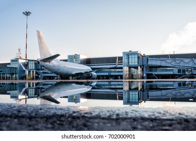 Passenger aircraft parked to a jetway with reflection in a puddle