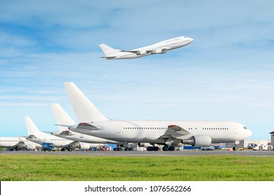 Passenger aircraft row, airplane parked on service before departure at the airport, other plane push back tow. One two-story airplane take off from the runway in the blue sky