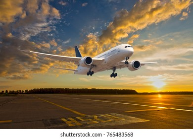 Passenger aircraft takes off from the airport runway. The airplane is climbing into the sunset sky.