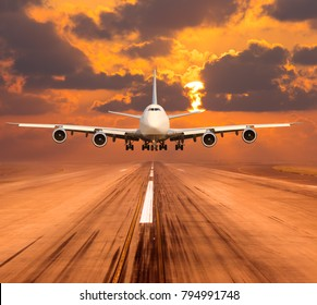 Passenger aircraft takes off from the airport runway. In the background orange sunset sky.
