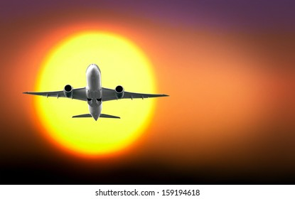 Passenger aircraft taking off with big yellow sun in background