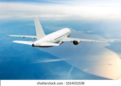 Passenger aircraft view from behind. The plane flies away. The airplane flies high above the river and boundless plain.