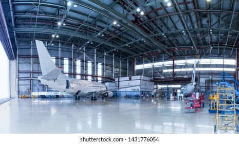 Passenger aircrafts under maintenance. Checking mechanical systems for flight operations. Panorama of airplanes in the hangar