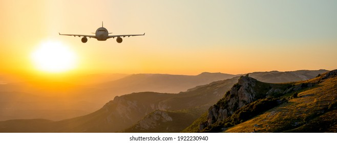 Passenger airliner fly on beauty sunrise or sunset mountain landscape, horizontal photo. Vacation air transportation concept