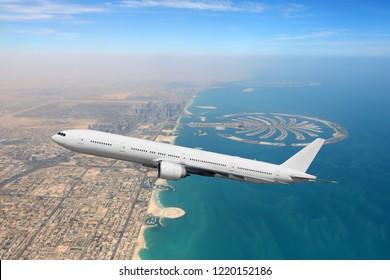 Passenger airliner flying over Dubai city and sea coastline