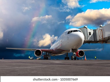 Passenger airplane at the airport runway against a bright blue sky and a rainbow. The plane is preparing for the flight.