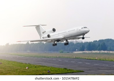 Passenger airplane with engines at the tail take off at sun on a runway