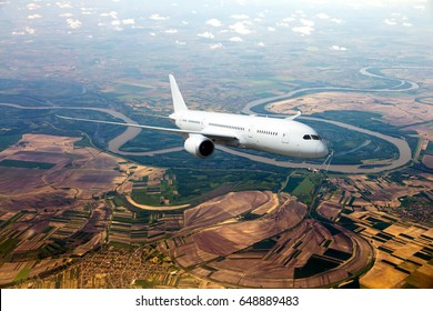 Passenger airplane in flight. Aircraft flies high over the bright green plain and river. Front view.