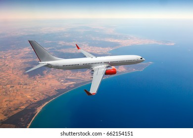 Passenger airplane in flight. Aircraft fly high over the ocean coast.