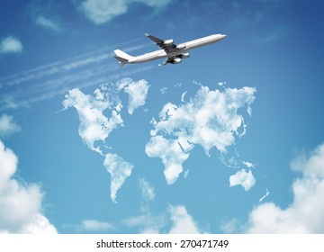 Passenger airplane flying above sky with clouds in shape of world map concept for travel and vacations
