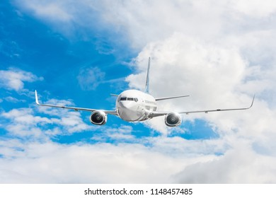 Passenger airplane flying at flight level high in the sky above the clouds and blue sky