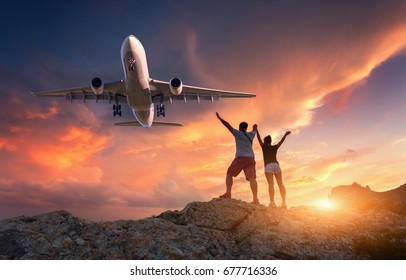 Passenger airplane and happy people on the mountain against colorful sky at sunset. Landscape with commercial airplane and standing man and woman with raised up arms in summer. Couple and aircraft