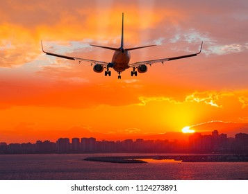 Passenger airplane landing to airport at sunset