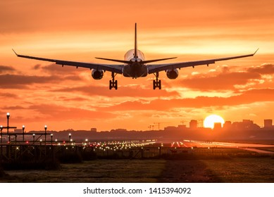 Passenger airplane is landing at the runway during a beautiful colorful and cloudy sunrise.