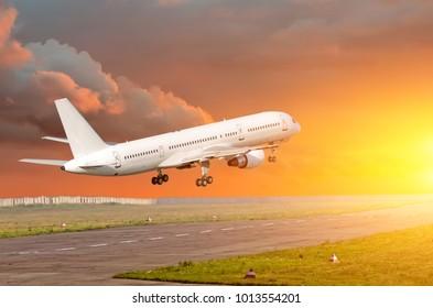 Passenger airplane landing at sunset on a runway