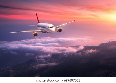 Passenger airplane. Landscape with big white airplane is flying in the red sky over the clouds and sea at colorful sunset. Passenger aircraft is landing at dusk. Business trip. Commercial plane.Travel