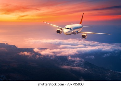 Passenger airplane. Landscape with big white airplane is flying in the sky over the clouds and sea at colorful sunset. Passenger aircraft is landing at dusk. Business trip. Commercial plane. Travel