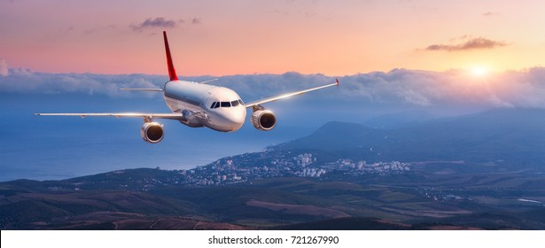 Passenger airplane. Landscape with white airplane is flying in the orange sky with clouds over mountains, sea at colorful sunset. Passenger aircraft is landing. Commercial plane. Private jet. Travel