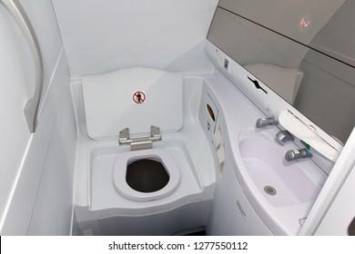 Passenger airplane lavatory. Toilet seat and wash basin closeup.