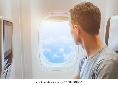 passenger of airplane looking at window, international travel, happy man tourist enjoy flight in comfortable air plane