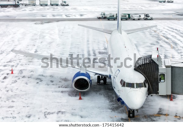 Passenger Airplane on the airfield winter before takeoff. Sleeve for boarding passengers in the aircraft