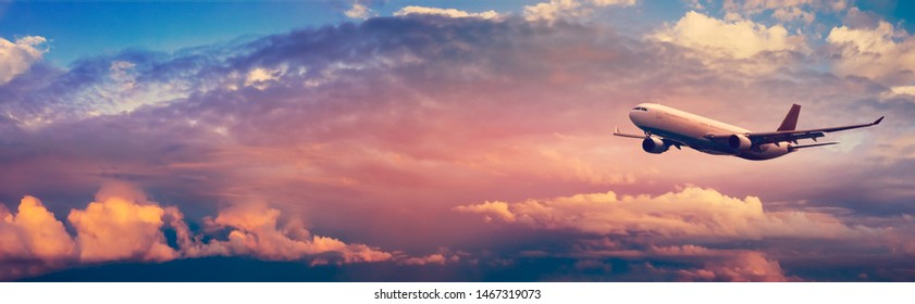 Passenger airplane on cloudy sky background in pastel colors with copy space. Wide landscape with aircraft in soft sunlight for your concept of air trip, journey or international air transportation.