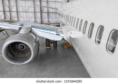 Passenger airplane on maintenance of jet engine and aircraft hangar