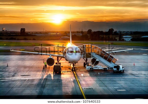 Passenger airplane on runway near the terminal in an airport at sunset time. Airport land crew doing flight service for passenger airplane at sunset time.
