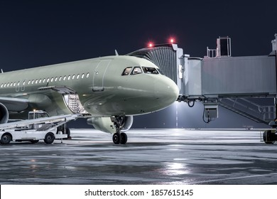 The passenger airplane stands at the jetway on an airport night apron. The baggage compartment of the aircraft is open and the luggage is being loaded