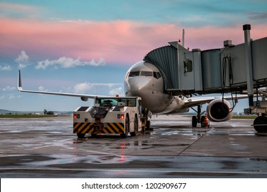 Passenger airplane and tow truck at the jet bridge. Front view