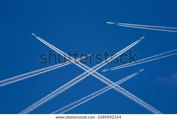 A lot of passenger airplanes on the air, busy air traffic, traveling high season starts concept. White planes against blue sky.  Photo manipulation.
