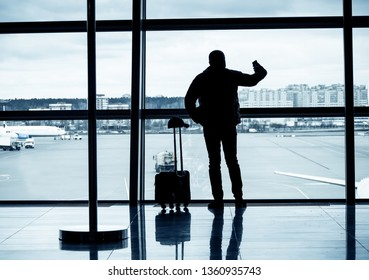 Passenger at an airport making a selfie using a smartphone