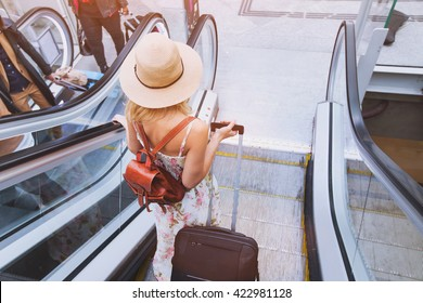 passenger in airport or modern train station, woman commuter travels with luggage