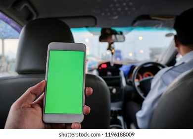 Passenger in back seat of Taxi with smartphone in hand for use mobile application.