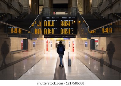 "Passenger with a backpack and a suitcase beside him/her is standing below a timetable board in a giant hall of a railway station in Milan, Italy. Text: ""Arrivals, Departures"". Solo traveling concept."