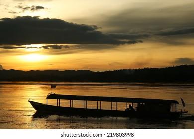 Passenger boat on the Mekong River in sunset