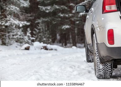 Passenger car with winter tires standing on snow-covered forest road, copy space