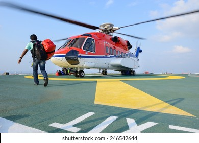 A passenger carry his baggage to embark helicopter at oil rig platform