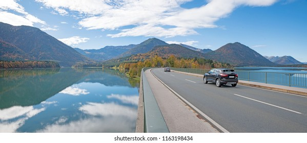 passenger cars driving over bridge, lake sylvenstein, in autumn. landscape bavaria
