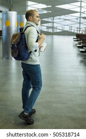 Passenger with Coffee Cup in Hand and Backpack  Sitting at the Hall of Airport Travel Concept